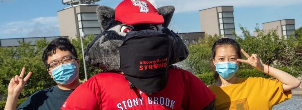 Stony Brook University, Stony Brook, NY: Wolfie and students pose in their masks in front of the Wang Center. Credit: Stony Brook University/John Griffin.
