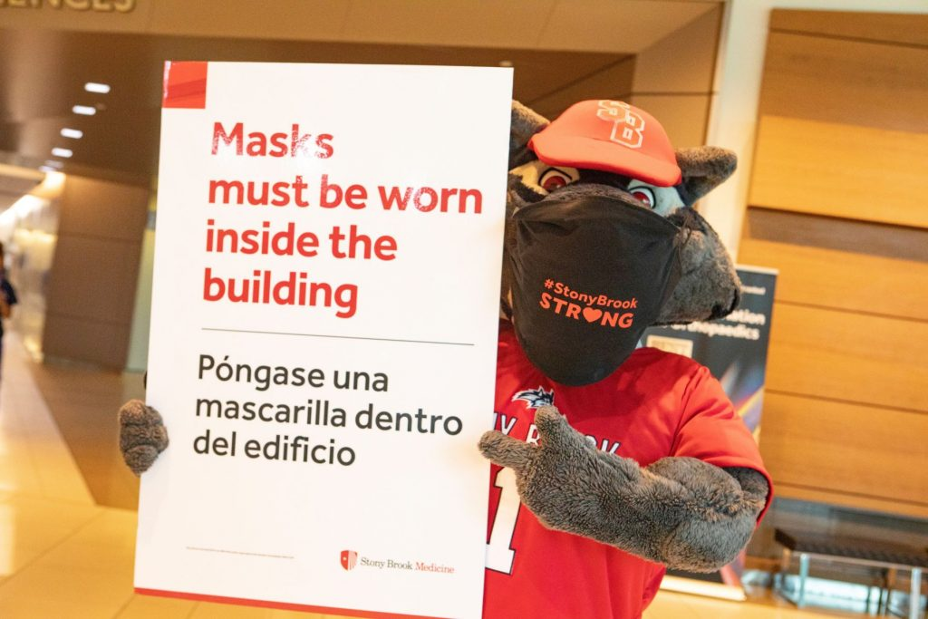 Wolfie wearing a mask and holding signage.