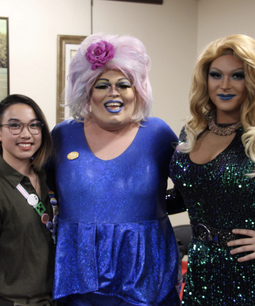 Drag queens posing for picture with student