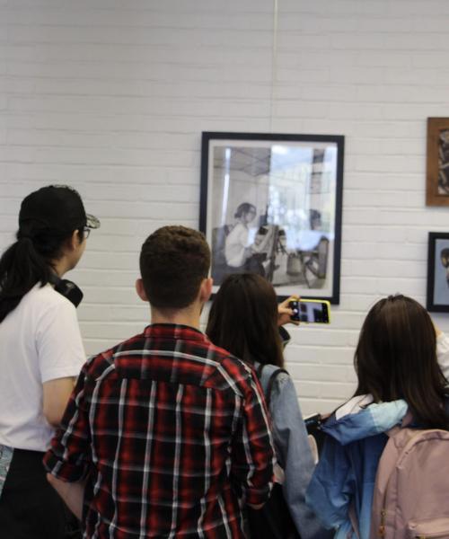 Students looking at artwork at Art Crawl