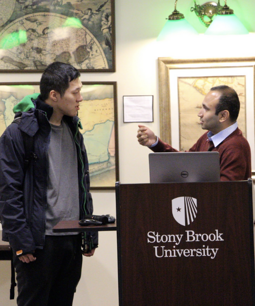 Dr. Kedar Kirane speaking with student in the front of the room