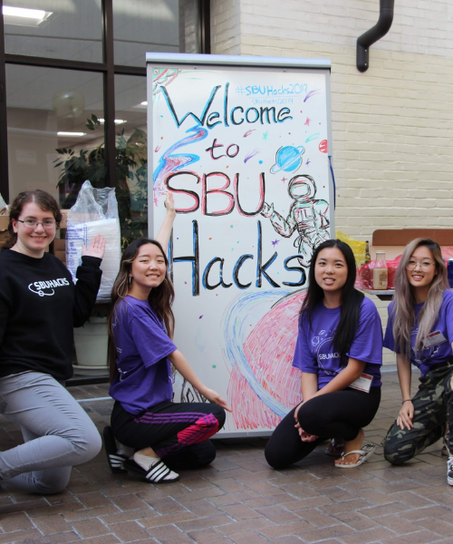 Students in front of SBU Hacks sign for a picture
