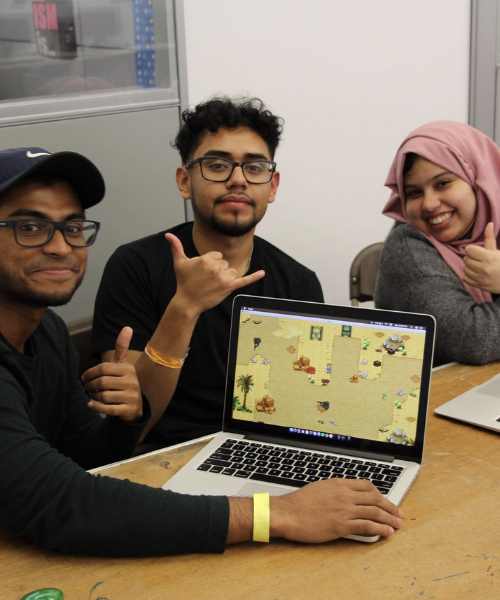 Students at hackathon posing for picture with a thumbs up